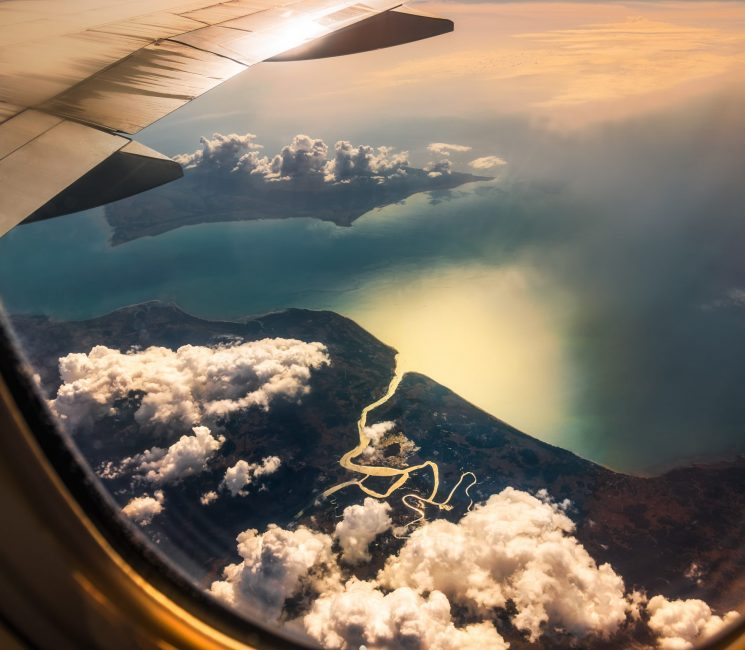 Aerial View from Window of Airplane. Flying above Clouds and Beautiful Land with River Delta and Sea at Sunrise.